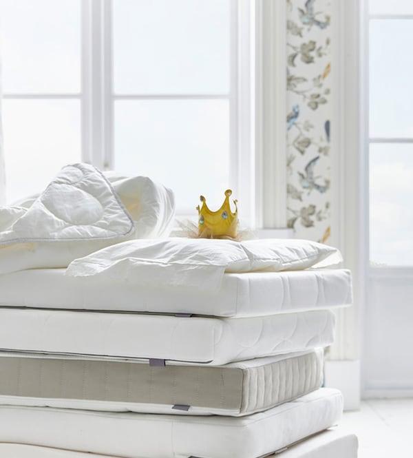 Madrasser står stablet i et lyst rum med blomstret taper. Øverst på madrasserne er en krone.