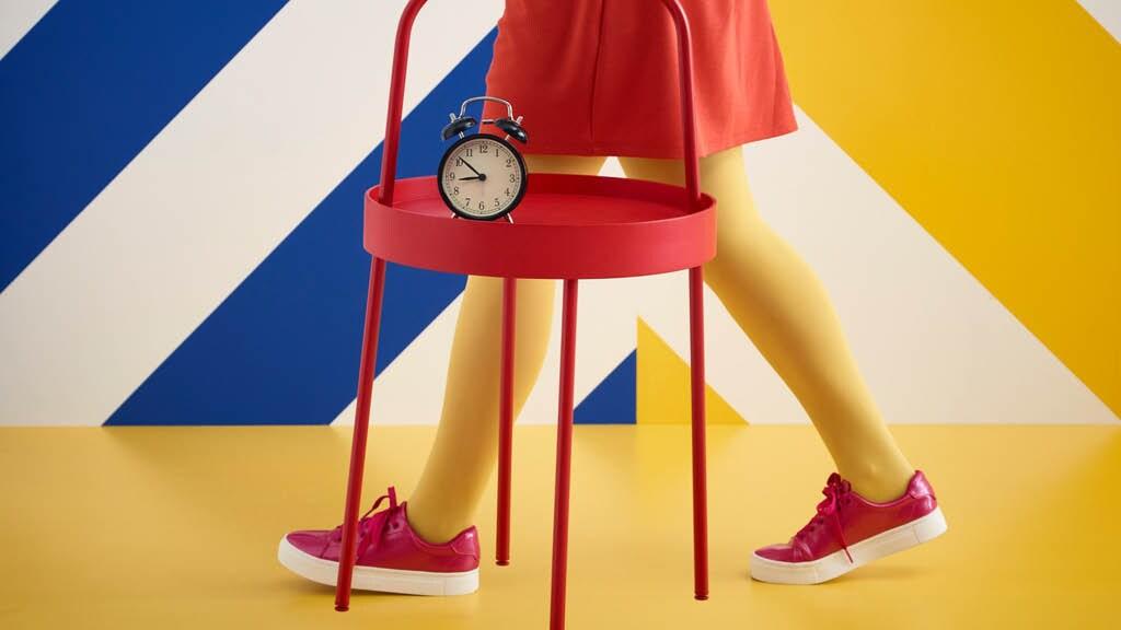 Mädchen trägt roten Beistelltisch mit Wecker vor einem bunten Hintergrund