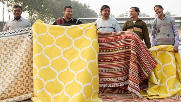 Männer halten eine Auswahl an handgewebten Teppichen.