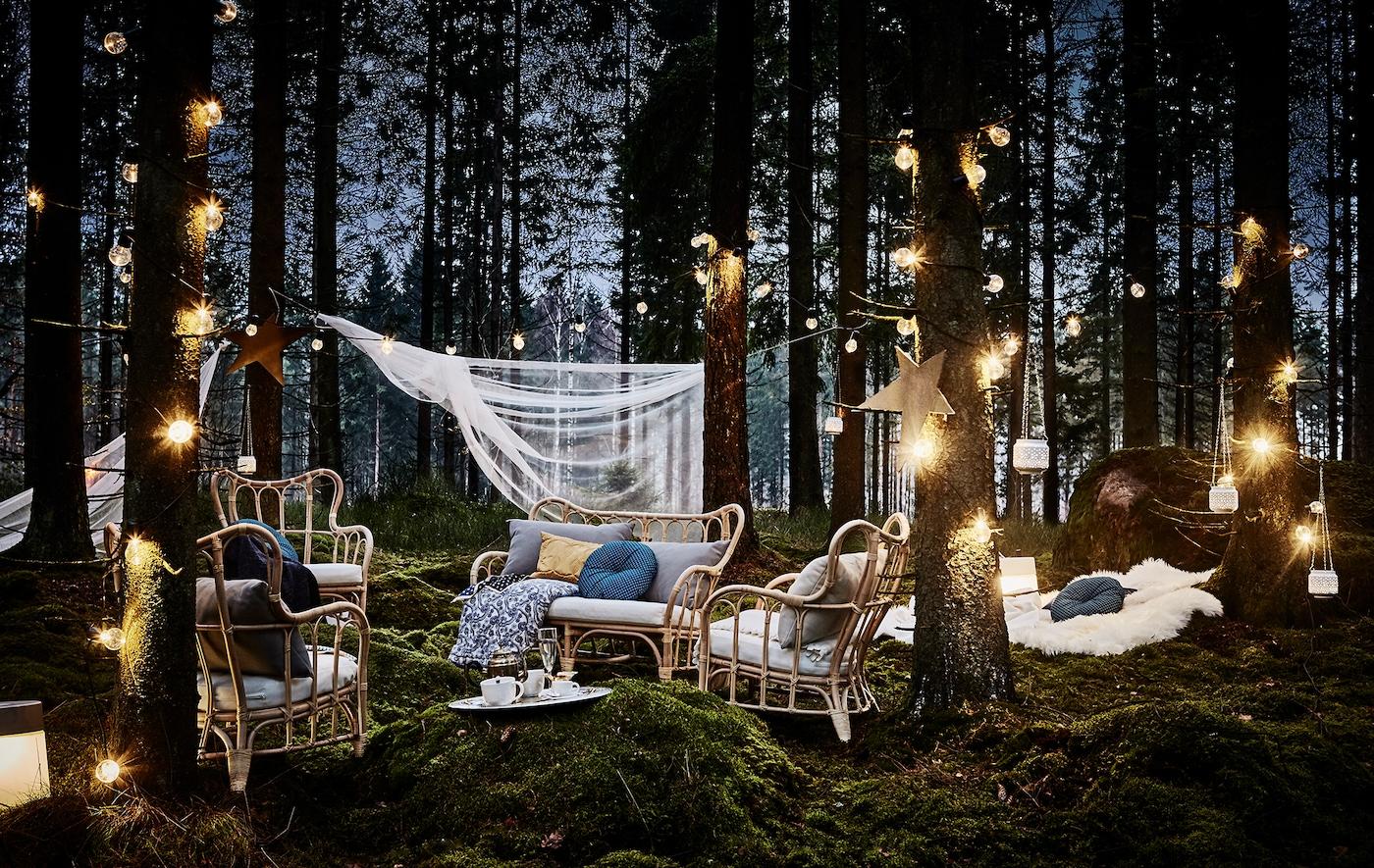 Märchenhafter Außenbereich im Wald mit Sesseln, Polstern, Decken & vielen Lichtern von IKEA.