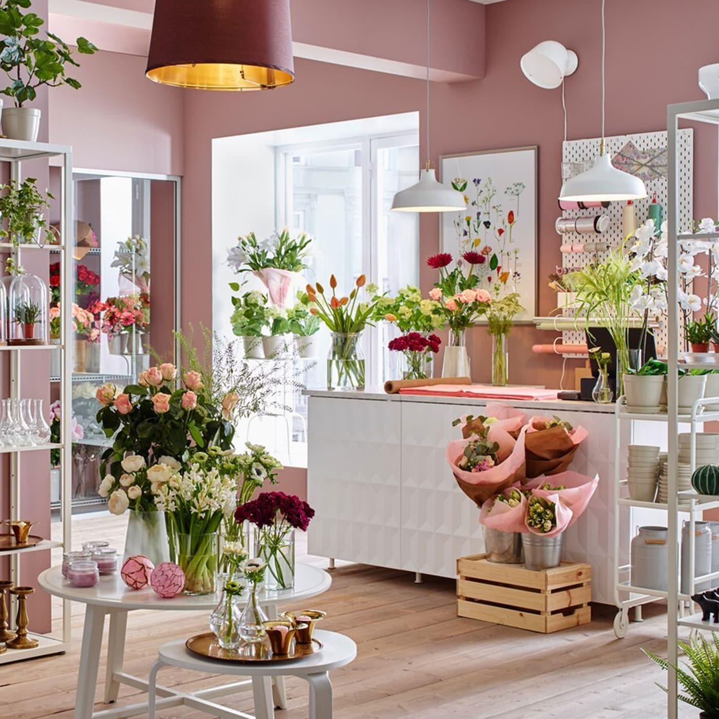Magasin de fleurs avec des murs roses et des étagères blanches.