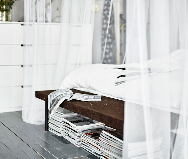 Magazines stacked underneath a cork bench at the end of the bedframe.