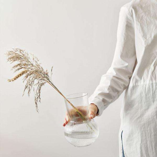 Main tendue tenant un vase PÅDRAG en verre transparent, avec épis de blé et herbes séchées.