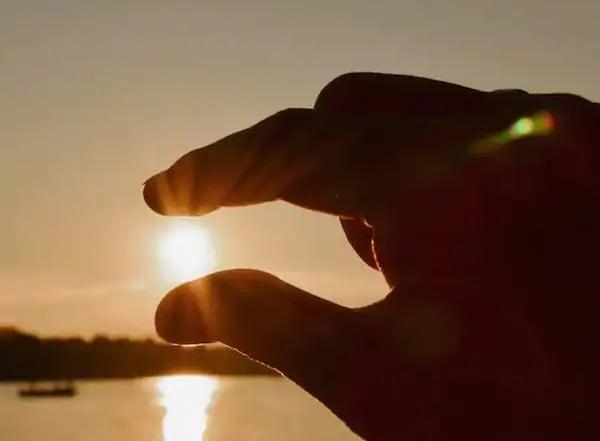 Main tentant d'attraper le soleil
