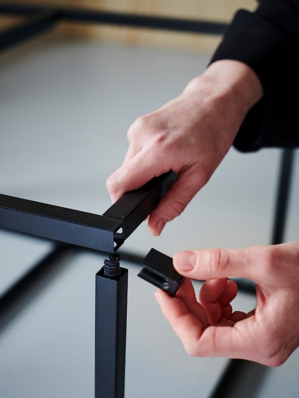 Mâini asamblând o ramă metalică neagră cu elemente de fixare cu pană.