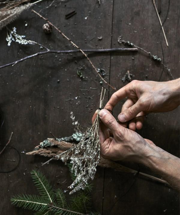 Mains en train d'assembler de petits rameaux avec du fil à coudre noir.