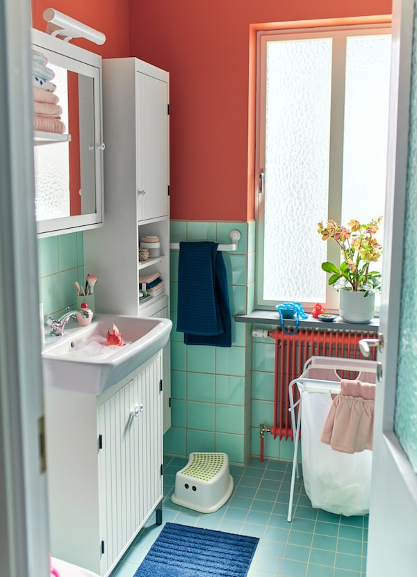 Make room in the bathroom with IKEA SILVERÅN white high cabinets with doors, and room for your laundry with JÄLL foldable white bag and plastic stand.