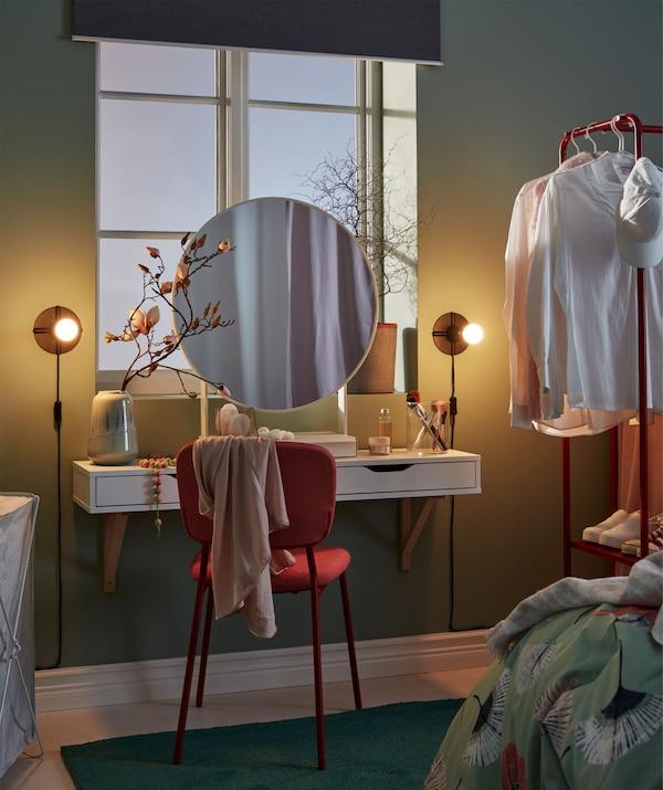 Makeupstation under et soveværelsesvindue, med et rundt spejl, en hylde med skuffer, brugt som et lille bord, en stol og en lampe.