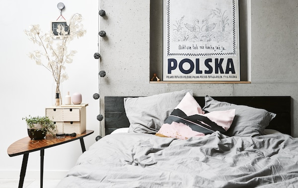 Makuuhuone, jossa parisänky ja sivupöytä.