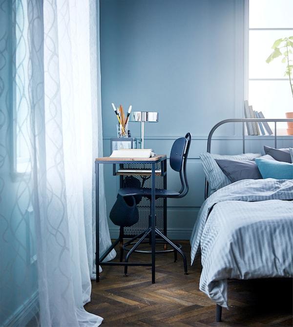 Makuuhuone, jossa pyörällinen massiivipuinen ja metallinen työpöytä sekä työtuoli sängyn ja seinän välissä.