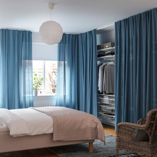 Makuuhuone, jossa tila on jaettu sinisävyisillä valoaläpäisevillä verhoilla.
