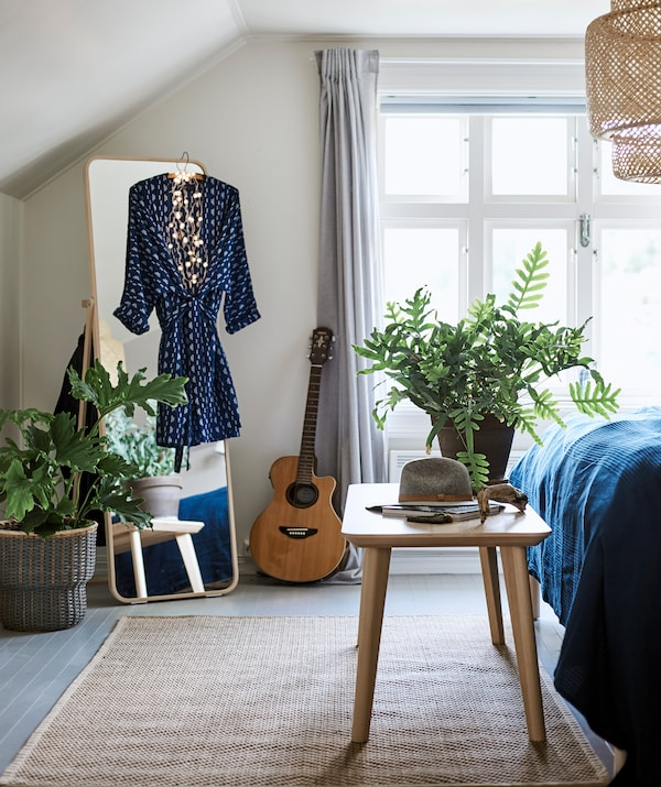 Makuuhuone kudotulla kattovalaisimella ja matolla, itsenäisesti seisova peili, jossa on roikkuu mekko ja penkki sängyn päässä.