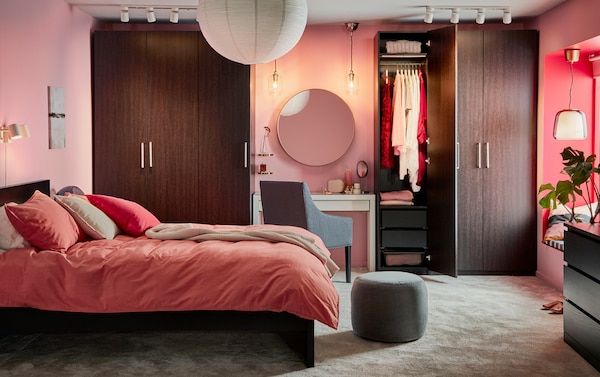 Makuuhuoneessa mustanruskea sängyn runko ja vaatekaapit,  valkoinen peilipöytä ja vaaleanpunaruskeat vuodetekstiilit.
