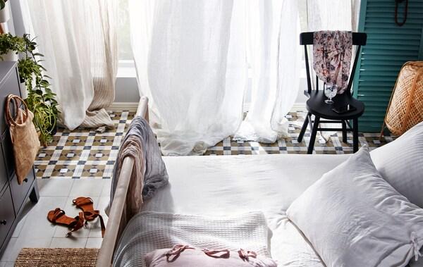 Makuuhuoneessa on avoimet, korkeat ikkunat, joiden edessä on ohuet verhot, jotka näyttävät heiluvan kevyessä tuulessa.