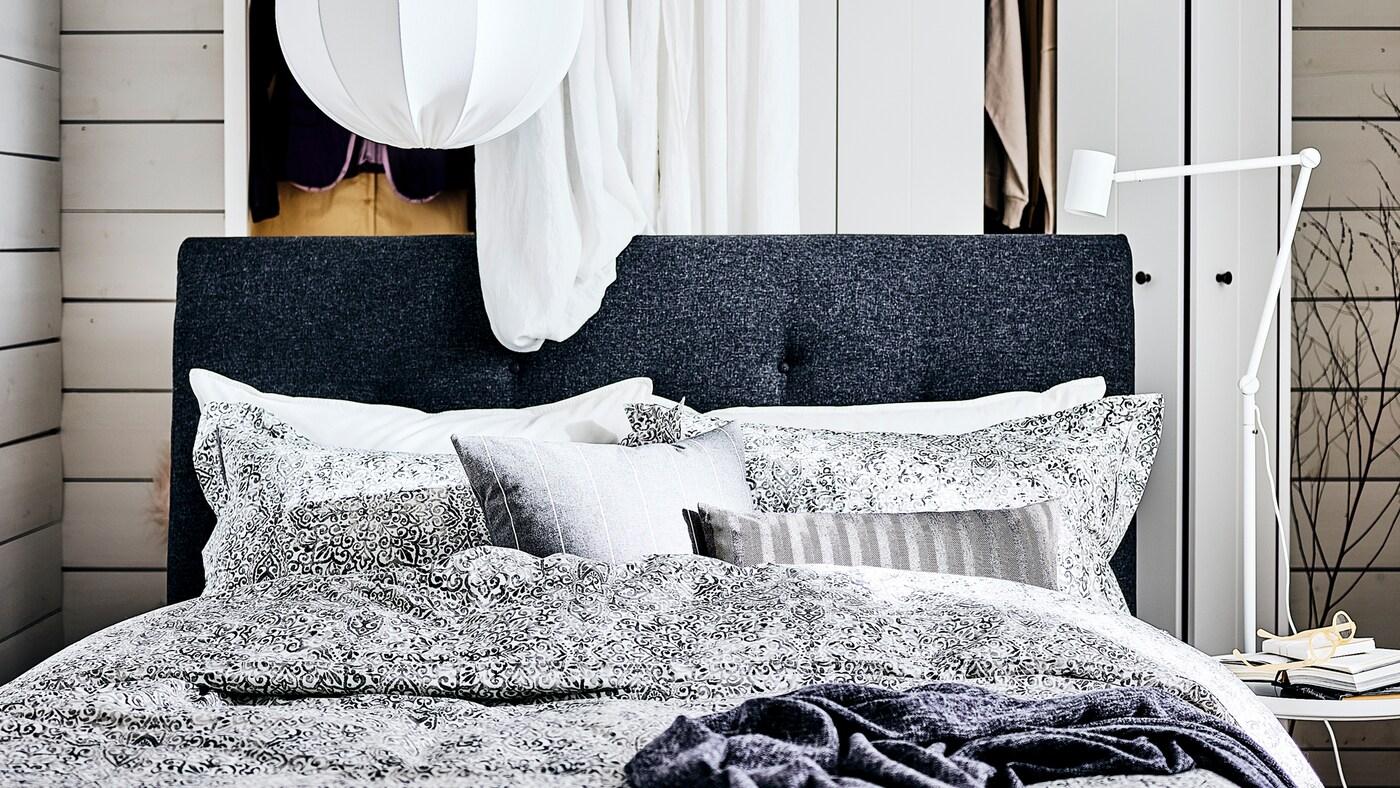 Makuuhuoneessa tummanharmaa verhoiltu IDANÄS-sängynrunko. Sen takana valkoinen verho ja valkoinen vaatekaappi, yllä valkoinen kattovalaisin.