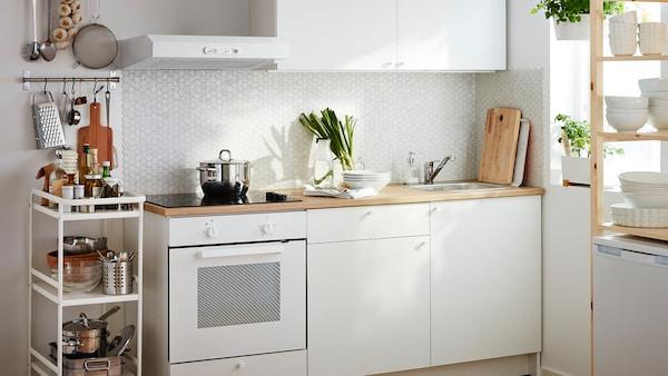 Malá biela kuchyňa so zabudovanou rúrou a spodnými skrinkami, zásuvkami, pracovnou doskou a nástennými skrinkami.