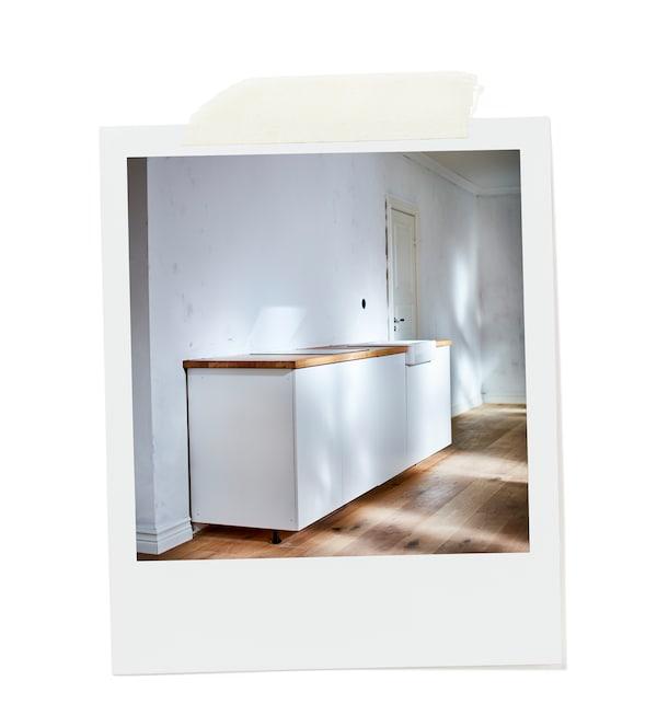 Malá biela kuchyňa v inak prázdnej miestnosti s drevenou podlahou a bielymi stenami.