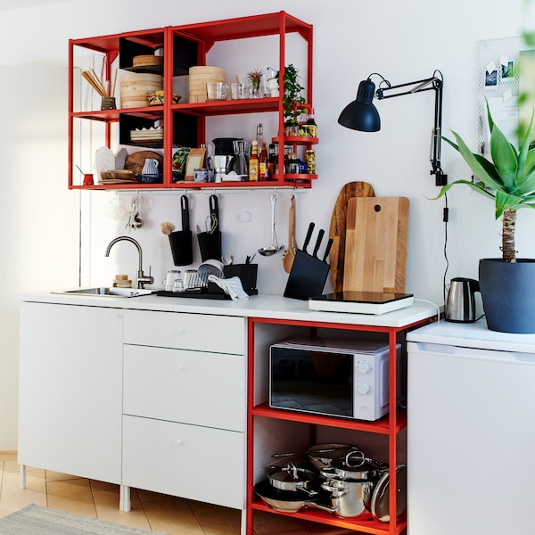 Mała czerwono-biała kuchnia z przenośną płytą indukcyjną, drewnianymi deskami do krojenia, czarną lampą ścienną i czarną suszarką do naczyń.