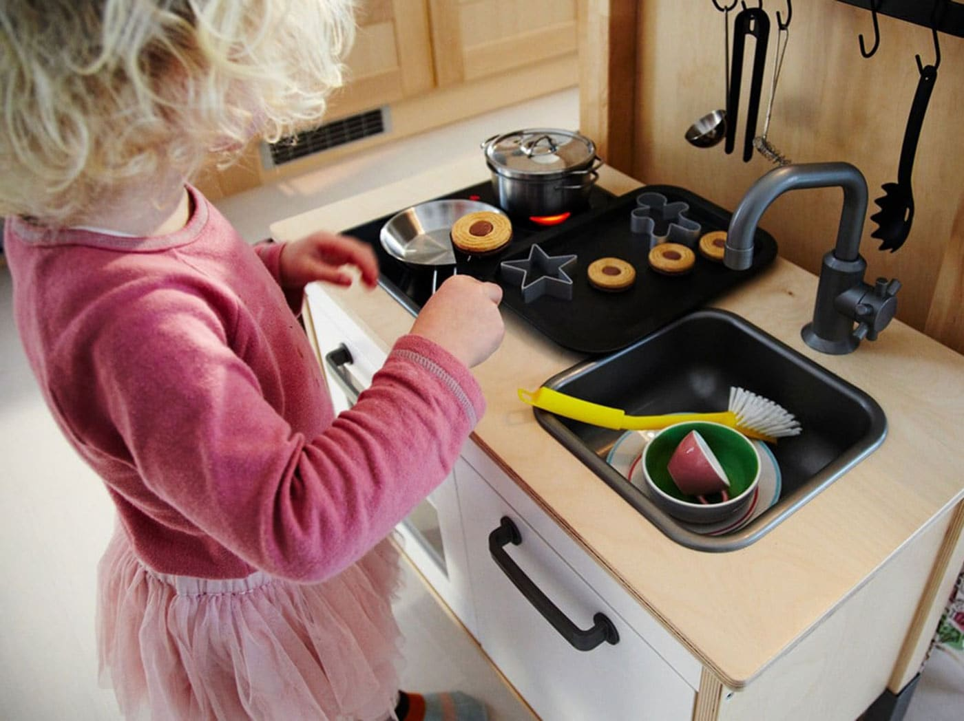 Malá holčička stojí u dětské kuchyně a vaří.