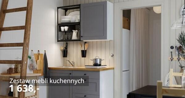 Mała kuchnia z antracytowymi otwartymi półkami, szarymi frontami, drewnianym blatem, czarnym stołem i dwoma drewnianymi krzesłami.