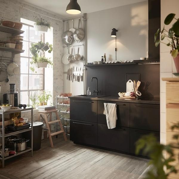 Mała kuchnia z czarnymi fronami i otwartym przechowywaniem.