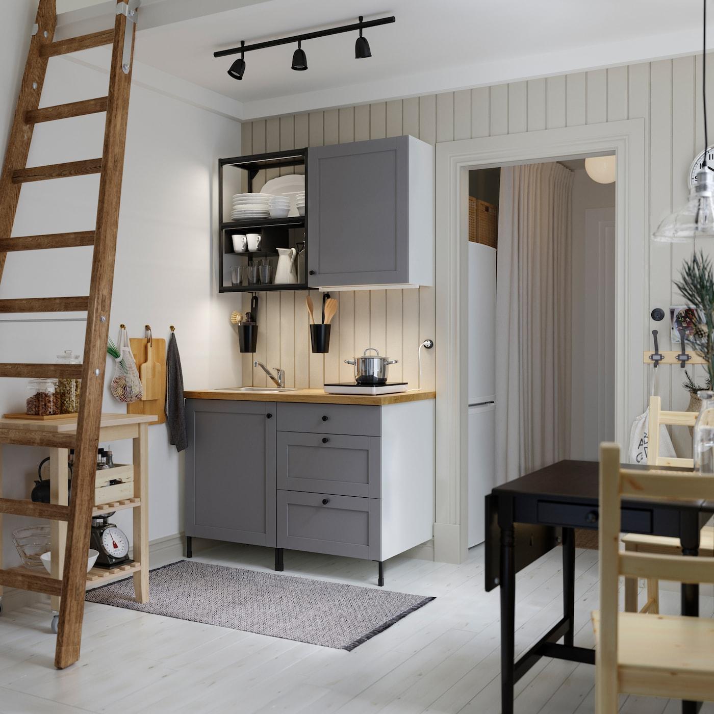 Mala kuhinja s otvorenim policama od antracita, sivi frontovi, drvena radna ploča, crni sto i dve drvene stolice.
