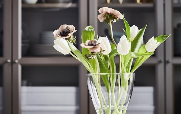 Malá kytica bielych tulipánov, hnedých makov a sviežich zelených listov v zaoblenej váze VASEN pred skrinkou.