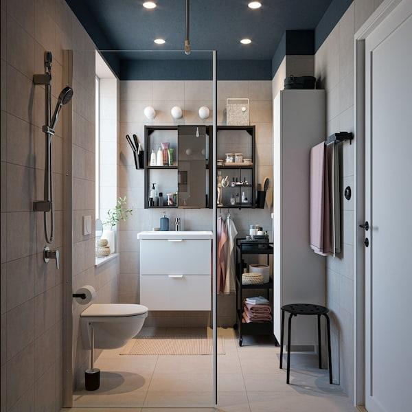 Mała łazienka z białą szafką z umywalkową, czarnym lustrem i prysznicem.