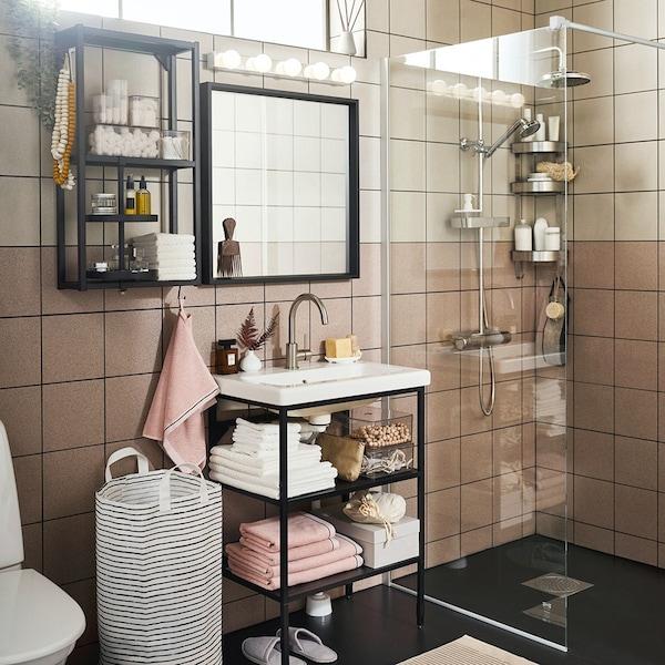 Mała łazienka z czarną szafką z umywalką, lustrem i prysznicem.