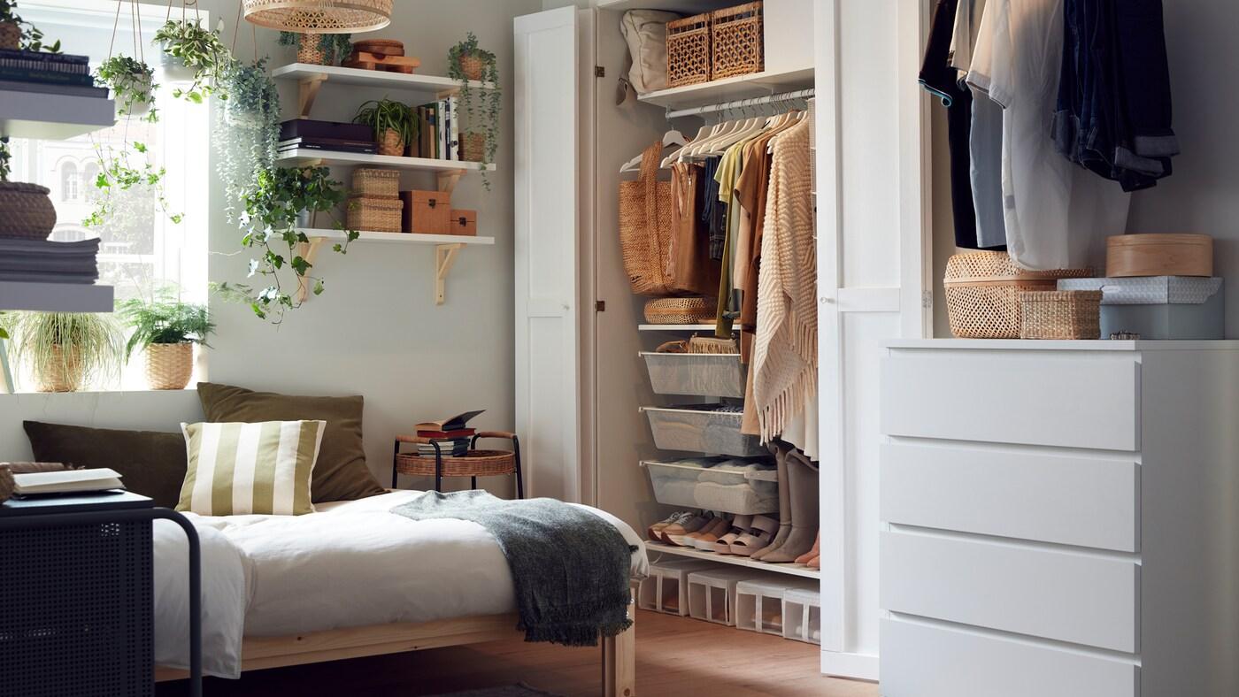 Malá ložnice s dřevěným rámem postele, šatní skříň s úhledně uspořádaným oblečením, police s krabicemi a rostlinami.