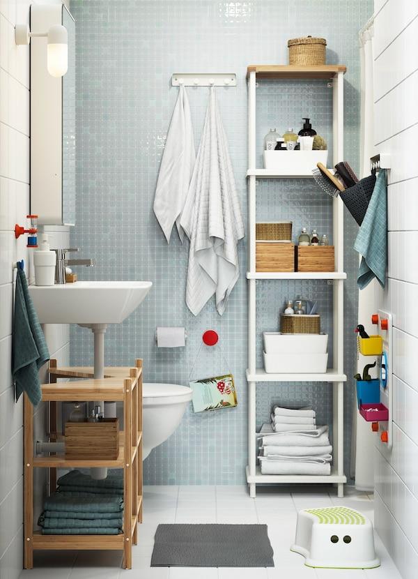 Mała rodzinna łazienka z białymi i błękitnymi płytkami oraz wysokim, białym regałem DYNAN wypełnionym akcesoriami łazienkowymi.