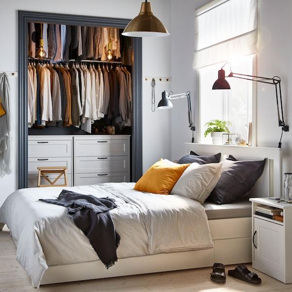 Mala siva i bela spavaća soba, s otvorenim ormanom i IKEA SONGESAND belim okvirom kreveta s 4 kutije za odlaganje.