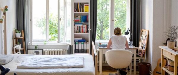 Mala, svetla spavaća soba s policom za knjige i radnim stolom za kojim sedi mlada žena, leđima okrenuta fotoaparatu.
