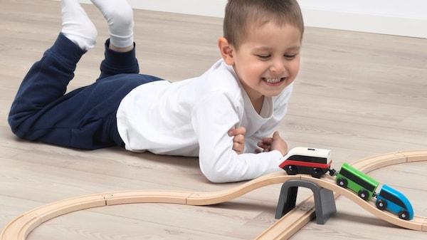 Мальчик играет в игрушечную железную дорогу в детской