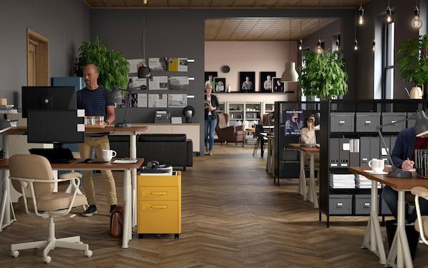 Małe biuro z beżowymi biurkami IDÅSEN o regulowanej wysokości, szarymi krzesłami obrotowymi ALEFJÄLL i brązowymi komodami IDÅSEN.