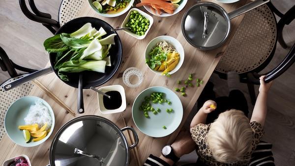 Malé dítě sedí dospělému na klíně u dřevěného stolu s mísami a nádobím a jí rukama kousky zeleniny.