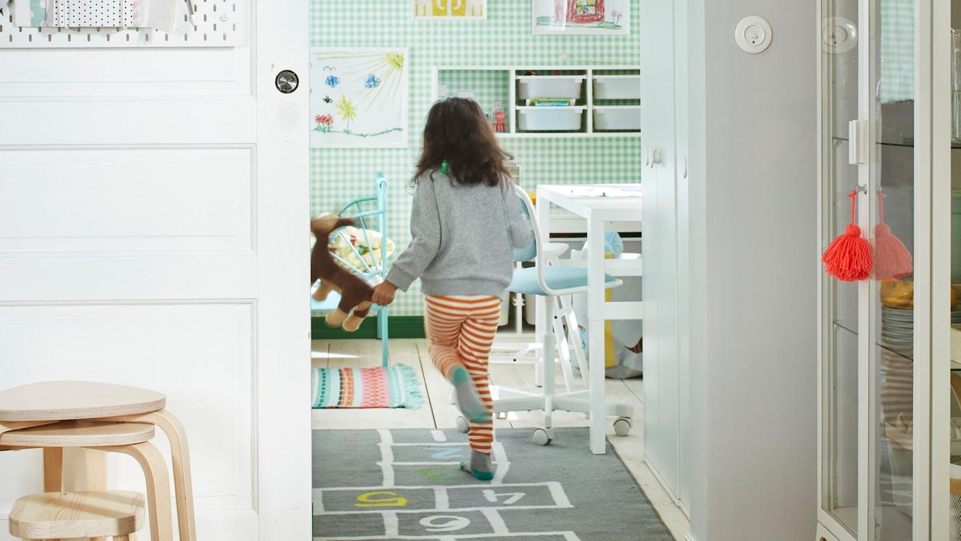 Małe dziecko wybiegające przez otwarte przesuwane drzwi prowadzące do biało-zielonego pomieszczenia z łóżkiem, szafkami, biurkiem i innymi meblami.