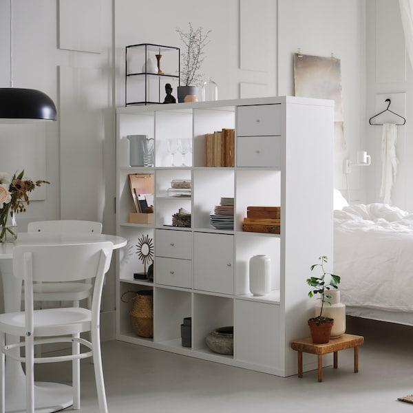 Małe mieszkanie ze strefą sypialnianą i jadalnianą przedzielone białym regałem KALLAX.