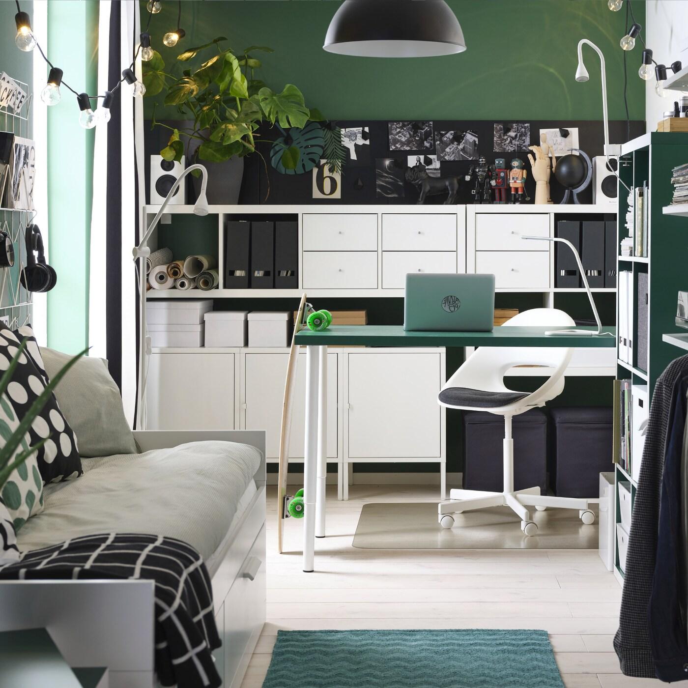 Маленькая комната в зеленой гамме: зеленый стол, белые стеллажи, кушетка, открытый гардероб и черный подвесной светильник.