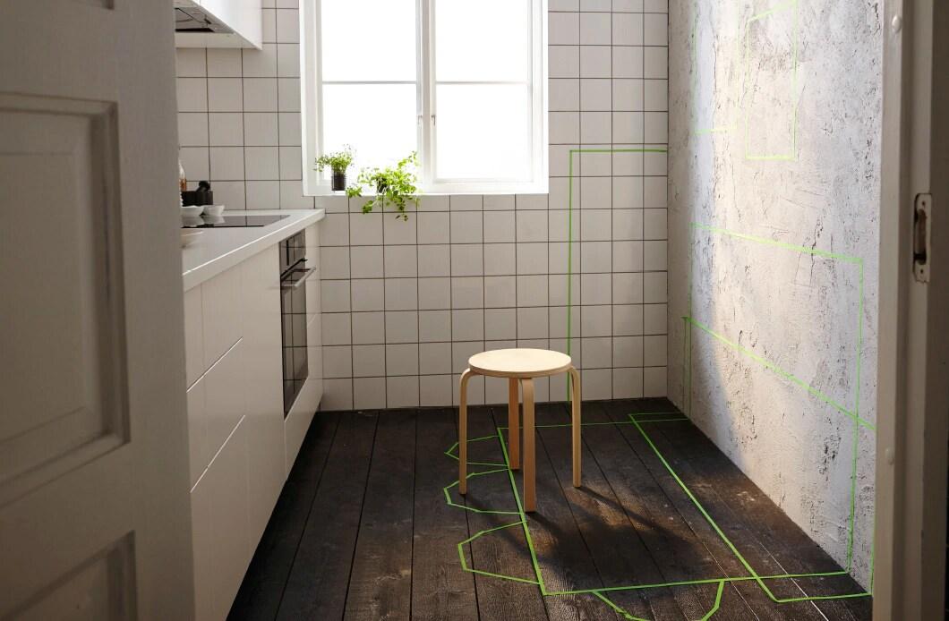 Маленькая кухня с одной свободной стеной. Зеленым скотчем помечено пространство для будущего размещения мебели для хранения, столов и стульев.