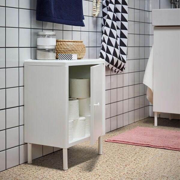 Mali bijeli element s otvorenim vratima, u njemu se nalazi toaletni papir. Na njemu nalaze se prozirne staklenke i mala košara od morske trave s poklopcem.