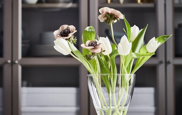 Mali buket bijelih tulipana, smeđih makova i svježeg zelenog lišća u zaobljenoj VASEN vazi ispred elementa.