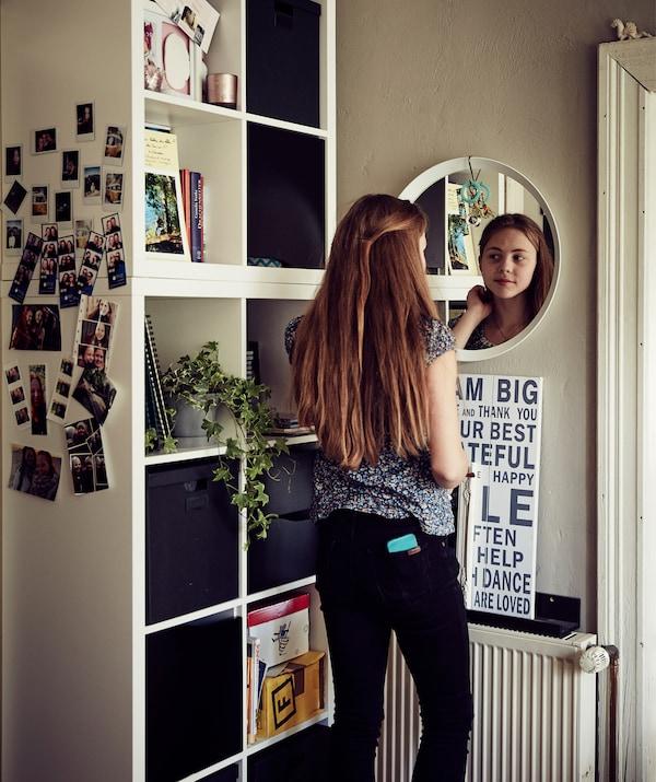 Malin تنظر في المرآة بجوار وحدة تخزين مكعبة.