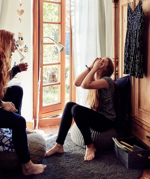 Malin وStine تجلسان سويًا وتضحكان بجوار أبواب فرنسية.