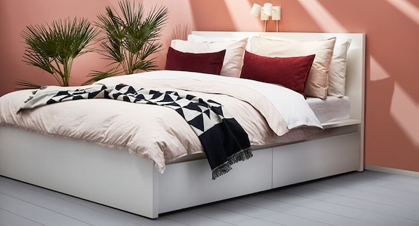 MALM queen high bed in white with four storage boxes, and sunlight shining through the room