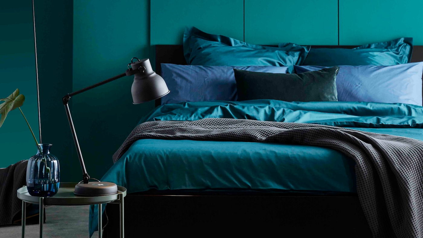 MALM säng med sängkläder inklusive mörkgrönt LUKTJASMIN påslakanset står mot en grön vägg i ett sovrum.