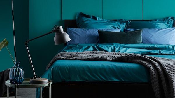 MALM-vuode, jossa on tummanvihreät LUKTJASMIN-liinavaatteet, vihreäseinäisessä makuuhuoneessa.