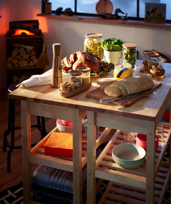 Mały, ale odświętny bufet na dwóch wózkach kuchennych ustawionych obok siebie; sztuczny kominek w tle.
