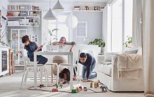 Malý byt, v němž si rodina hraje s vláčkem LILLABO. Místnost je vybavena postelí, pohovkou, stolem, malou kuchyňkou a úložnými díly.