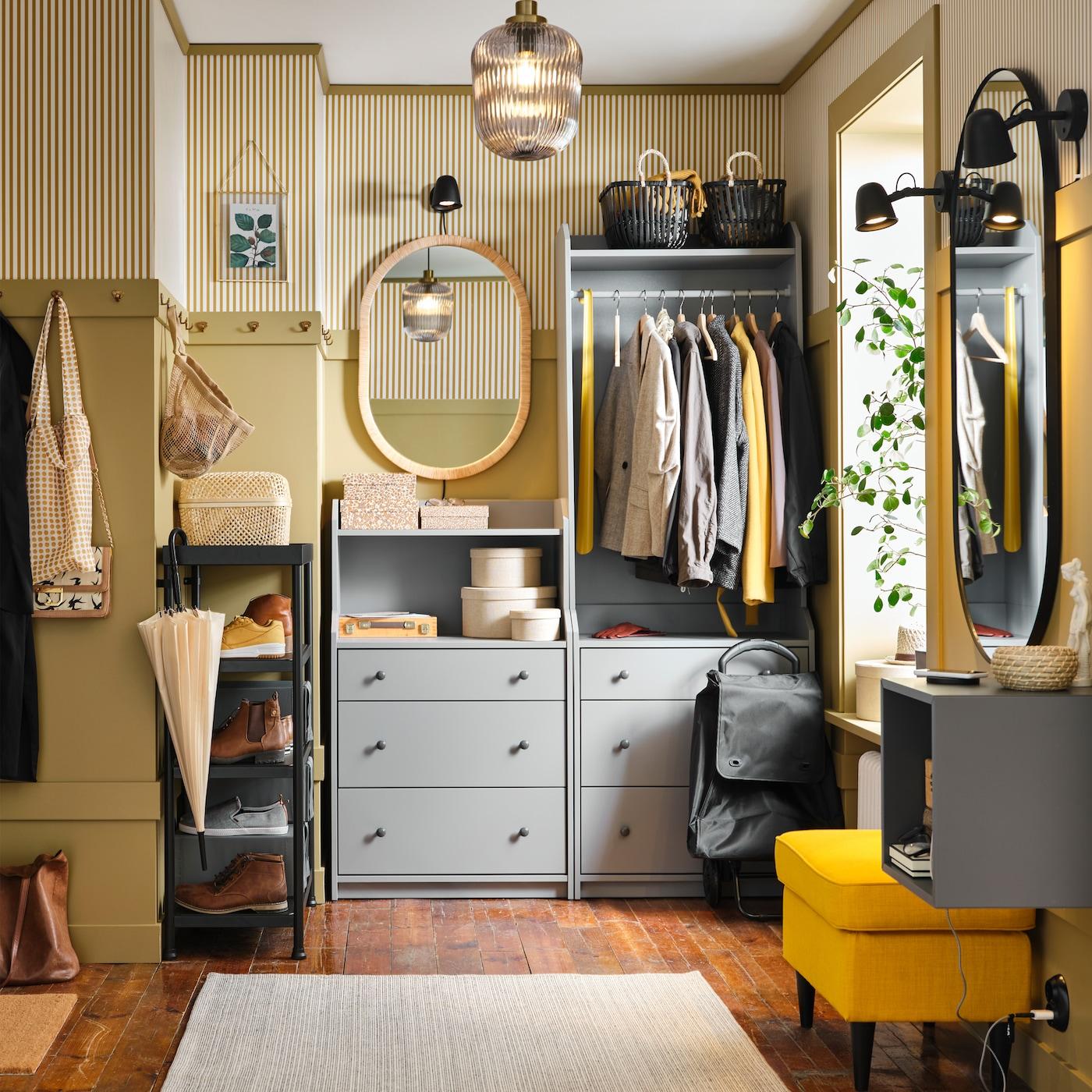 Mały korytarz z otwartymi półkami, szarym zestawem mebli do przechowywania i haczykami w kolorze mosiądzu.